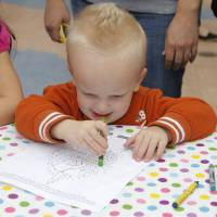 Photo - Levi Wilson, 2, of Oklahoma City, colors during Malee's first birthday celebration.