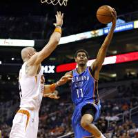 Photo - Jeremy Lamb, right, shoots over Marcin Gortat during the first half of Tuesday's preseason game in Phoenix. AP Photo