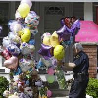 Photo - A Cleveland policeman carries balloons and flowers to the front porch of a home awaiting the arrival of Amanda Berry Wednesday, May 8, 2013, in Cleveland. Berry, 27, Michelle Knight, 32, and DeJesus,  had apparently been held captive in the house since their teens or early 20s, police said. (AP Photo/Tony Dejak)
