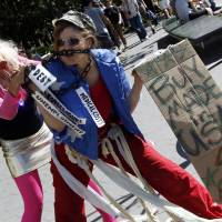 Photo -   Activist associated with the Occupy Wall Street movement perform a skit during a gathering of the movement in Washington Square park, Saturday, Sept. 15, 2012 in New York. The Occupy Wall Street movement will mark it's first anniversary on Monday. (AP Photo/Mary Altaffer)