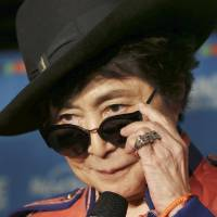 Photo - Yoko Ono adjusts her sunglasses as she speaks during a campaign to fight childhood hunger around the world, in Tokyo Thursday, Dec. 5, 2013. The 80-year-old widow of John Lennon said that she believes he would be happy to see his song