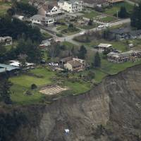 Photo - An aerial photo shows a landslide near Coupeville, Wash. on Whidbey Island, Wednesday, March 27, 2013. The slide severely damaged one home and isolated or threatened more than 30 on the island, about 50 miles north of Seattle in Puget Sound. No one was reported injured in the slide, which happened at about 4 a.m. Wednesday. (AP Photo/Ted S. Warren)