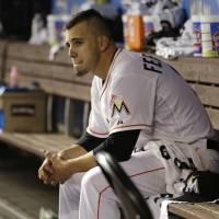 Photo - FILE - In this April 29, 2014 file photo, Miami Marlins starting pitcher Jose Fernandez sits in the dugout after pitching eight innings against the Atlanta Braves, in Miami.  More than a dozen major league pitchers have needed Tommy John surgery this year, a group that includes All-Stars Patrick Corbin, Josh Johnson and Matt Moore. NL Rookie of the Year Jose Fernandez is among three others headed to elbow ligament-replacement surgery, joining an illustrious group that includes Chris Carpenter (2007), Stephen Strasburg (2010), Adam Wainwright (2011) and Matt Harvey (2013). (AP Photo/File)
