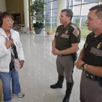 Photo - Nenita Mijares thanks Highway Patrol Troopers Steve Johnson (center) and Ken Pittman at the Norman Regional Healthplex on Thursday, April 21, 2011, in Norman, Okla.  The troopers performed CPR on her husband Hector Mijares, a retired commercial airline pilot, while working a multi-vehicle accident at Interstate 35 and 27th Street in Moore, OK.  The couple are living in Oklahoma City after retiring in the Philippines. Photo by Steve Sisney, The Oklahoman ORG XMIT: KOD