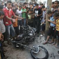 Photo -   Palestinians gather a round the wreckage of motorcycle following an Israeli air strike in Rafah, southern Gaza Strip, Sunday, Oct. 7, 2012. Israel's military says it has fired on two Gaza members of an al-Qaida-inspired group identified as having been involved in rocket attacks and an infiltration from Egypt. Palestinians say one man was killed. The military said they were involved in