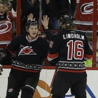 Photo - Carolina Hurricanes' Jeff Skinner, left, celebrates his goal against the Toronto Maple Leafs with Elias Lindholm (16), of Sweden, during the first period of an NHL hockey game in Raleigh, N.C., Thursday, Jan. 9, 2014. Carolina won 6-1. (AP Photo/Gerry Broome)