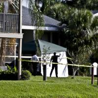Photo - Investigators stand outside an apartment complex where a man was fatally shot when a team of FBI agents swarmed his home early  Wednesday, May 22, 2013, in Orlando, Fla. The FBI says the man, being questioned by authorities in the Boston bombing probe, was fatally shot when he initiated a violent confrontation. (AP Photo/John Raoux)