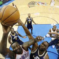 Photo - Oklahoma City Thunder center Kendrick Perkins, left, shoots in front of Utah Jazz center Al Jefferson, right, in the first quarter of an NBA basketball game in Oklahoma City, Friday, Nov. 30, 2012. Oklahoma City won 106-94. (AP Photo/Sue Ogrocki) ORG XMIT: OKSO108