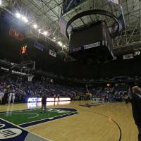 Photo - Teams stand near their benches as the arena is lit only by emergency lights after a power outage during the second half of an NCAA college basketball game between North Carolina and Wake Forest at the Atlantic Coast Conference tournament in Greensboro, N.C., Thursday, March 6, 2014. (AP Photo/Chuck Burton)