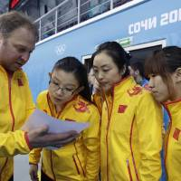 Photo - Team China coach Marcel Rocque, of Canada, talks with his players, from left, Wang Bingyu, Yue Qingshuang, and Jiang Yilun, after the first day of curling training at the 2014 Winter Olympics, Saturday, Feb. 8, 2014, in Sochi, Russia. (AP Photo/Robert F. Bukaty)