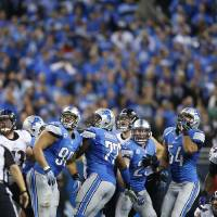 Photo - The Detroit Lions defensive line and the Baltimore Ravens look towards the end zone after Ravens kicker Justin Tucker, far right, kicked a 61-yard field goal to lead the game during the fourth quarter of an NFL football game in Detroit, Monday, Dec. 16, 2013. (AP Photo/Rick Osentoski)