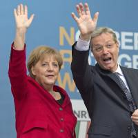 Photo -   File - In this May 9, 2012 file picture German Chancellor Angela Merkel, left, waves to the crowd as she attends an election campaign rally together with Norbert Roettgen, right, top candidate of the Christian Democratic Union party CDU for the North Rhine-Westphalia federal state elections in Gelsenkirchen, Germany. Germany's most populous state holds an election Sunday May 13, 2012 , with polls pointing to likely re-election for a center-left regional government that Chancellor Angela Merkel has sought to label as irresponsibly spendthrift. About 13.2 million people are eligible to vote for the state legislature in North Rhine-Westphalia in western Germany, which includes Cologne, Duesseldorf and the industrial Ruhr region. (AP Photo/Martin Meissner,File)