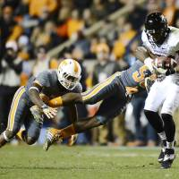 Photo - Vanderbilt wide receiver Jordan Matthews (87) is brought down by Tennessee defensive back JaRon Toney, left, and defensive lineman Jacques Smith (55) after pulling in a pass reception in the first quarter of an NCAA college football game on Saturday, Nov. 23, 2013, in Knoxville, Tenn. (AP Photo/Mark Zaleski)
