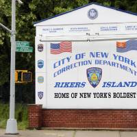Photo - FILE - In this May 17, 2011, file photo, a man walks near the sign at the entrance to the Rikers Island jail in New York. Jerome Murdough, a 56-year-old mentally ill inmate at Rikers Island jail,