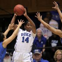 Photo - Duke's Ka'lia Johnson (14) looks to pass between DePaul's Jessica January, left, and Centrese McGee, right, during the first half of their second-round game in the NCAA basketball tournament in Durham, N.C., Monday, March 24, 2014.  (AP Photo/Ted Richardson)