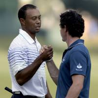 Photo -   Tiger Woods, left, and Rory McIlroy, of Northern Ireland, clasp hands on the 18th green after finishing the first round of the Tour Championship golf tournament Thursday, Sept. 20, 2012, in Atlanta. (AP Photo/David Goldman)