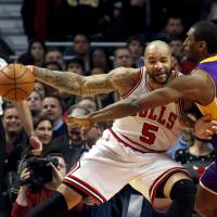 Photo - Los Angeles Lakers forward Metta World Peace (15) challenges Chicago Bulls forward Carlos Boozer (5) during the first half of an NBA basketball game, Monday, Jan. 21, 2013, in Chicago. (AP Photo/Charles Rex Arbogast)