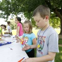Photo -  Six-year-old Ashlyn Gideon and Samuel Fett, 9, color plastic boomerangs at the 2013 vacation Bible school gatherings hosted by First Baptist Church of Edmond at area parks such as this one at Spring Hill Park in Edmond. Photo by Paul Hellstern, The Oklahoman   PAUL HELLSTERN -