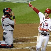 Photo -   Washington Nationals' Bryce Harper, right, reacts after crossing home plate on a solo home run, next to St. Louis Cardinals catcher Yadier Molina in the third inning of Game 5 of the National League division baseball series on Friday, Oct. 12, 2012, in Washington. (AP Photo/Nick Wass)