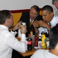 Photo -   FILE - In this June 24, 2010 file photo, President Barack Obama and Russia's President Dmitry Medvedev, left, eat burgers at Ray's Hell Burger in Arlington, Va. Call it the Obama effect: a presidential visit can be good advertising for the restaurants and businesses. Interest in where and what Obama and his family does can be explained with one word: authenticity. (AP Photo/Charles Dharapak, File)