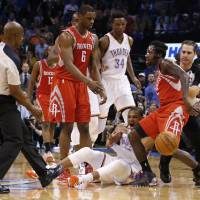 Photo - Oklahoma City Thunder guard Russell Westbrook, bottom, reacts after a foul by Houston Rockets guard Pat Beverley, right, during the first quarter of an NBA basketball game in Oklahoma City, Tuesday, March 11, 2014. Looking on are Rockets forward Terrence Jones (6) and Thunder center Hasheem Thabeet (34). (AP Photo/Sue Ogrocki)