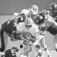 Photo - Cleveland Brown running back Greg Pruitt was the center of the Steelers attention as he ran for four yards and a first down in first quarter action Sunday, Nov. 13, 1977. Steelers Joe Greene, left, and Dwight White put the squeeze on Pruitt. The Brown later kicked  a field goal. (AP Photo) ORG XMIT: APHS43024