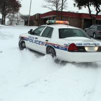 Photo - A Lawton, Okla., police cruiser tries to navigate the snow as blizzard conditions hit southwest Oklahoma at midday Tuesday, Dec. 25, 2012. (AP Photo/The Lawton Constitution, Brandon Neris)