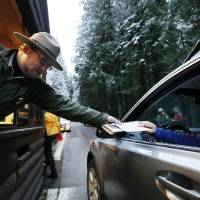 Photo - FILE - In this Jan. 7, 2012 file photo, Mount Rainier  National Park Ranger Matt Chalup, left, hands park information to one of the first visitors to the park at the Nisqually entrance near Ashford, Wash. The politics have been fierce and the fingerpointing incessant. Come March 1, the across-the-board federal spending cuts called sequestration go into effect, launching a new season of economic uncertainty for a nation still trying to shake off a recession. A look at the cuts, how much they amount to and who they will affect -- in question and answer form. (AP Photo/Elaine Thompson, File)