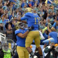 Photo -   UCLA quarterback Brett Hundley, right, jumps into the arms of tight end Joseph Fauria after Fauria scored a touchdown during the first half of their NCAA college football game against USC, Saturday, Nov. 17, 2012, in Pasadena, Calif. (AP Photo/Mark J. Terrill)
