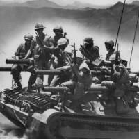 """Photo - FILE -In this July 3, 1968 file photo, Marines of the first battalion, ninth marines ride on a lightweight tank-like vehicle carrying four 106mm recoilless rifles near Khe Sanh in Vietnam. The Marine Corps is holding a deactivation ceremony on Friday, Aug. 29, 2014, for the 1st Battalion, 9th Marine Regiment, 2nd Marine Division, a battalion nicknamed the """"Walking Dead."""" (AP Photo/Stone)"""