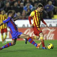 Photo - Barcelona's Lionel Messi from Argentina duels for the ball with Levante's Vyntra from the Czech Republic during their La Liga soccer match at the Ciutat de Valencia stadium in Valencia, Spain, Sunday, Jan. 19, 2014. (AP Photo/Alberto Saiz)