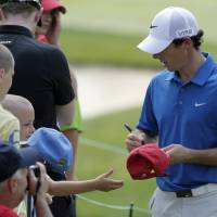 Photo - CORRECTS SPELLING TO MCILROY, INSTEAD OF MCILLROY - Rory McIlroy, of Northern Ireland, signs autographs for fans during the pro-am for the the Memorial golf tournament Wednesday, May 28, 2014, in Dublin, Ohio. (AP Photo/Jay LaPrete)