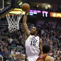 Photo - Utah Jazz's Derrick Favors (15) dunks the ball as Cleveland Cavaliers' Shaun Livingston (14) looks on in the fourth quarter during an NBA basketball game Saturday, Jan. 19, 2013, in Salt Lake City. The Jazz defeated the Cavaliers 109-98. (AP Photo/Rick Bowmer)