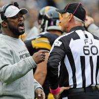 Photo -   Pittsburgh Steelers head coach Mike Tomlin, left, talks with field judge Gary Cavaletto (60) during a timeout in the second quarter of an NFL football game against the Philadelphia Eagles in Pittsburgh, Sunday, Oct. 7, 2012. The Steelers won 16-14. (AP Photo/Gene J. Puskar)