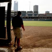 Photo - Monte McCoy, head groundskeeper of the Oklahoma City RedHawks, walks onto the field at the Chickasaw Bricktown Ballpark in Oklahoma City.  Photo by Bryan Terry, The Oklahoman