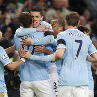 Photo - Manchester City's Stevan Jovetic, facing, celebrates after scoring the opening goal with teammates during the English FA Cup fifth round soccer match against Chelsea at the Etihad Stadium, Manchester, England, Saturday, Feb. 15, 2014. (AP Photo/Jon Super)