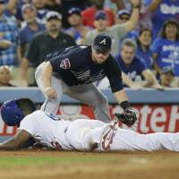 Photo - Los Angeles Dodgers' Yasiel Puig, bottom, safely takes third base after hitting a triple as Atlanta Braves third baseman Chris Johnson watches during the fifth inning of a baseball game on Tuesday, July 29, 2014, in Los Angeles. (AP Photo/Jae C. Hong)