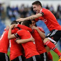 Photo - Benfica players celebrate after scoring the opening goal during their Portuguese league soccer match with Belenenses Sunday, March 2 2014, at Belenenses' Restelo stadium in Lisbon. Benfica defeated Belenenses 1-0 to remain at the top of the table. (AP Photo/Armando Franca)