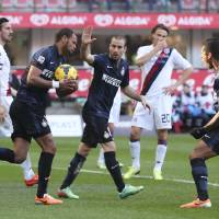 Photo - Inter Milan defender Jorge Rolando, second from left, of Portugal, holds the ball after scoring during the Serie A soccer match between Inter Milan and Cagliari at the San Siro stadium in Milan, Italy, Sunday, Feb. 23, 2014. (AP Photo/Antonio Calanni)