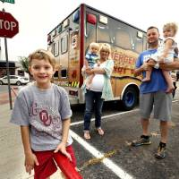 Photo - Hurts Donut Co. owners Kas and Tim Clegg and their children Grayson, 7, and 22 month-old twins Finnegan and Harper stand in front of their delivery van.  STEVE SISNEY