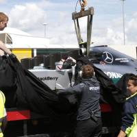 Photo - Mechanics cover the car of Germany's Nico Rosberg of Mercedes following  the British Formula One Grand Prix at Silverstone circuit, Silverstone, England, Sunday, July 6, 2014. Rosberg failed to complete the race due to mechanical failure. Britain's Lewis Hamilton of Mercedes won the race, Finland's Valtteri Bottas of Williams finished second and Australia's Daniel Ricciardo of Red Bull finished third.(AP Photo/Lefteris Pitarakis)