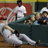 Photo - Cincinnati Reds right fielder Jay Bruce makes a sliding catch in foul territory for an out on Houston Astros' Jose Altuve in the ninth inning of a baseball game Wednesday, Sept. 18, 2013, in Houston. (AP Photo/Pat Sullivan)