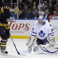 Photo - Buffalo Sabres center Cody Hodgson (19) gets hit with an incoming shot as he screens Toronto Maple Leafs goaltender James Reimer during the first period of an NHL hockey game in Buffalo, N.Y., Thursday, March 21, 2013. (AP Photo/Gary Wiepert)
