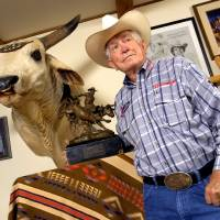 Photo - RODEO / BULL / BULL RIDING: ** ADVANCE FOR SATURDAY, SEPT. 15 ** Sixteen-time world bull riding champion Jim Shoulders is pictured with the mounted head of a bull, Bufford T Lite, and one of his Calgary Stampede championship bull riding trophies in his home in Henryetta, Okla., Wednesday, Sept. 6, 2006. (AP Photo/Tulsa World, Stephen Holman) ORG XMIT: OKTUL101