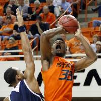 Photo - Oklahoma State's Marcus Smart (33) shoots over UC Davis' Corey Hawkins (3) during the men's college basketball game between Oklahoma State and UC Davis at  Gallagher-Iba Arena in Stillwater, Okla., Friday, Nov. 9, 2012. Photo by Sarah Phipps, The Oklahoman
