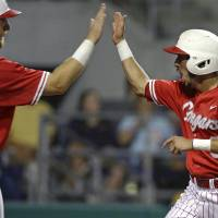 Photo - Houston's Caleb Barker (27) ands Josh Vidales greet each other after they both scored on a two-run RBI double by Connor Hollis in the third inning of an NCAA college baseball regional tournament game against LSU in Baton Rouge, La., Monday, June 2, 2014. (AP Photo/Gerald Herbert)