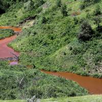 Photo - Saltwater leaks into this stream after running downhill, Thursday, July 10, 2014, near Mandaree, N.D. A pipeline leak on Fort Berthold Indian Reservation spilled 1 million gallons of saltwater, a byproduct of oil and gas production. Company officials say the leak likely started over the Fourth of July weekend. (AP Photo/Tyler Bell)