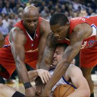 Photo - Golden State Warriors' David Lee, center, tries to keep a loose ball from Los Angeles Clippers' Lamar Odom, left, and Eric Bledsoe during the first half of an NBA basketball game in Oakland, Calif., Monday, Jan. 21, 2013. (AP Photo/Marcio Jose Sanchez)