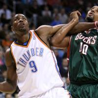 Photo - OKLAHOMA CITY THUNDER / MILWAUKEE BUCKS / NBA BASKETBALL  Oklahoma City Thunder forward Serge Ibaka battles Milwaukee's Kurt Thomas during the Thunder - Bucks game November 27, 2009 in the Ford Center in Oklahoma City.    BY HUGH SCOTT, THE OKLAHOMAN ORG XMIT: KOD