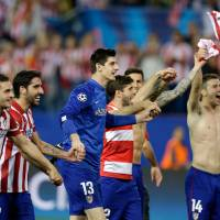 Photo - Atletico players celebrate at the end of the Champions League quarterfinal second leg soccer match between Atletico Madrid and FC Barcelona in the Vicente Calderon stadium in Madrid, Spain, Wednesday, April 9, 2014. Atletico defeated Barcelona 1-0. (AP Photo/Paul White)
